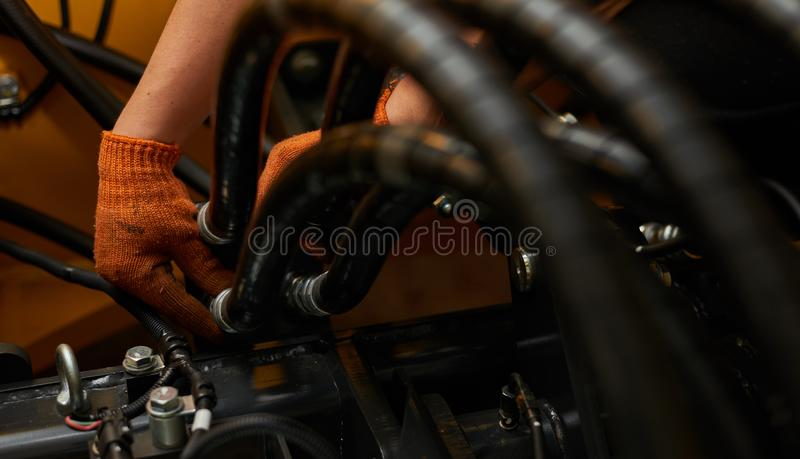 Low key photo of hydraulic pipes maintenance on heavy industry machine stock image