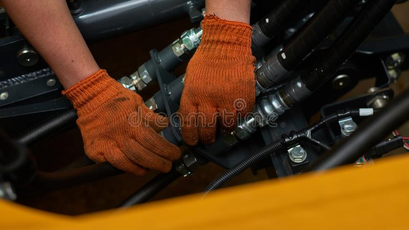 Low key photo of hydraulic pipes maintenance on heavy industry machine royalty free stock images