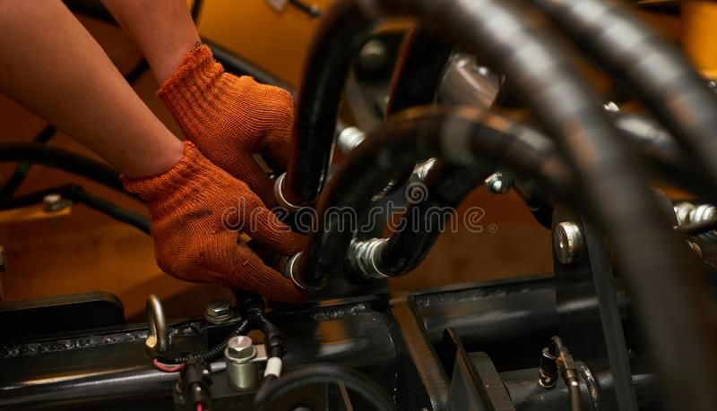 Low key photo of hydraulic pipes maintenance on heavy industry machine stock images