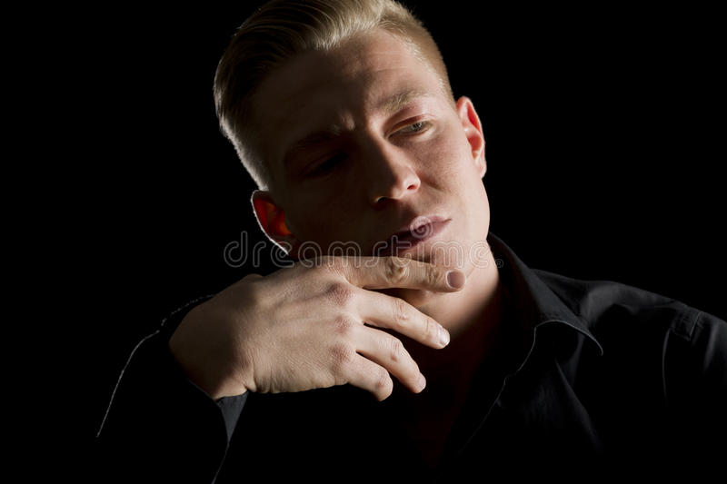 Low key portrait of contemplative young man looking aside. stock photo