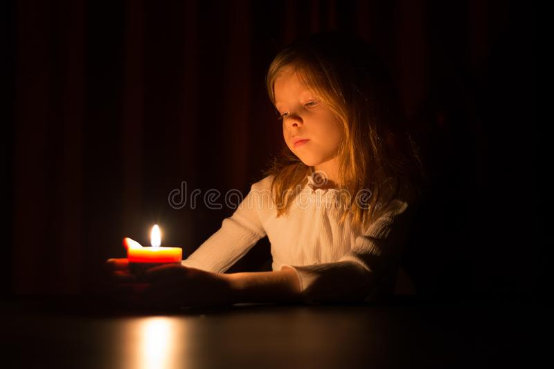 The cute little blonde girl is looking on the light of candle over dark background stock image