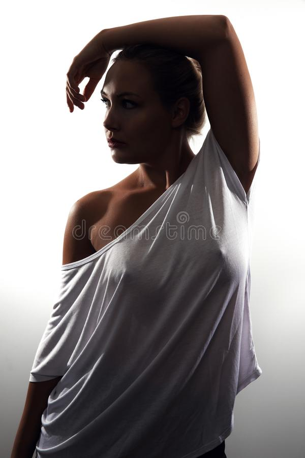 Low-key studio portrait of gorgeous woman with blonde hair and white t-shirt stock photos