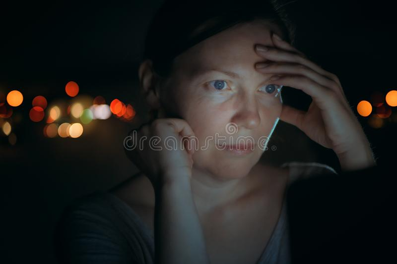 Low key portrait of tired woman looking at laptop screen stock photo