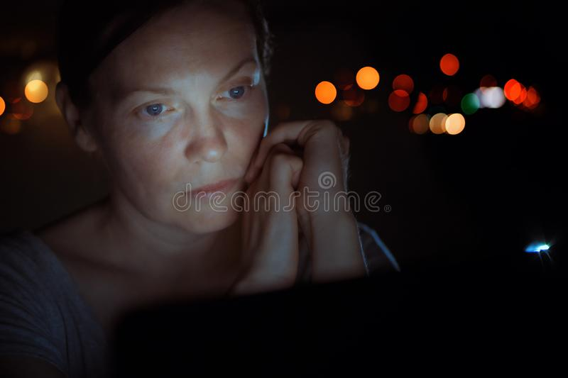 Low key portrait of tired woman looking at laptop screen stock image