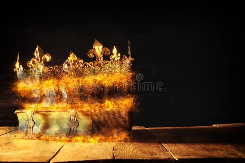 Low key of queen/king crown burning over old books. vintage filtered. fantasy medieval period. Low key of queen/king crown burning over old books. vintage stock photography