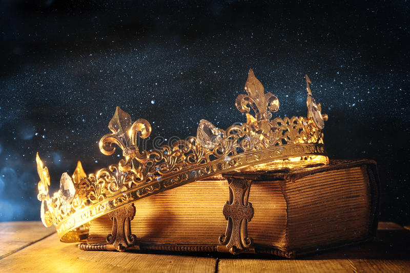 Low key of queen/king crown on old book. vintage filtered. fantasy medieval period. Low key image of beautiful queen/king crown on old book. vintage filtered royalty free stock photo
