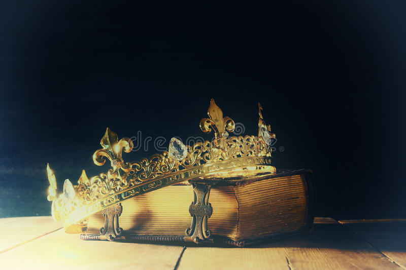 Low key of queen/king crown on old book. vintage filtered. fantasy medieval period. Low key image of beautiful queen/king crown on old book. vintage filtered royalty free stock photography