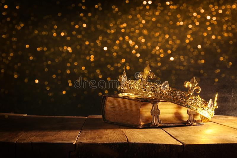 Low key of queen/king crown on old book. vintage filtered. fantasy medieval period. Low key image of beautiful queen/king crown on old book. vintage filtered stock image