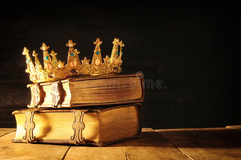 Low key of queen/king crown on old books. vintage filtered. fantasy medieval period. Low key image of beautiful queen/king crown on old books. vintage filtered stock photos