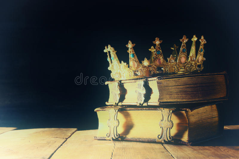 Low key of queen/king crown on old books. vintage filtered. fantasy medieval period. Low key image of beautiful queen/king crown on old books. vintage filtered royalty free stock photo