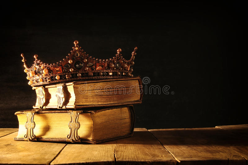 Low key of queen/king crown on old books. vintage filtered. fantasy medieval period. Low key image of beautiful queen/king crown on old books. vintage filtered royalty free stock photos