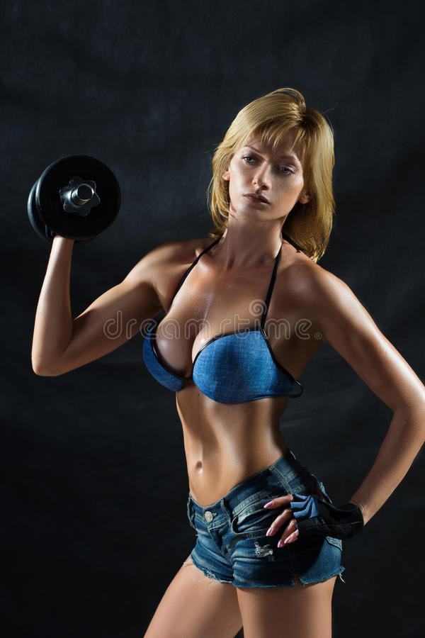 Low key silhouette of a fitness young woman. boobs. Low key silhouette of a fitness woman with dumbbells stock images
