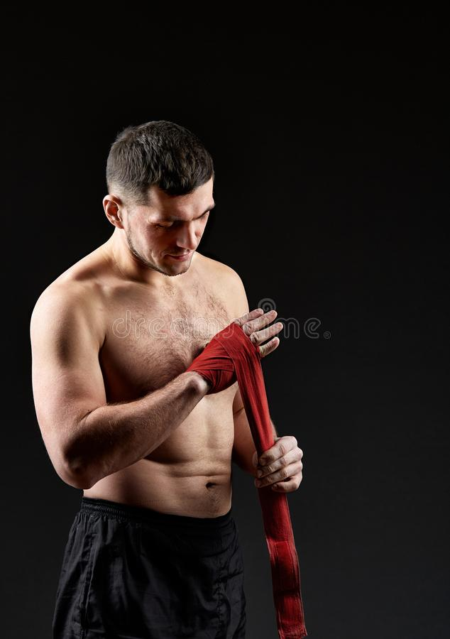 Low key studio portrait of handsome muscular fighter practicing boxing on dark blurred background stock photo
