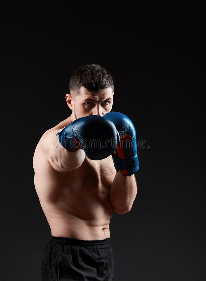 Low key studio portrait of handsome muscular fighter practicing boxing on dark blurred background stock image