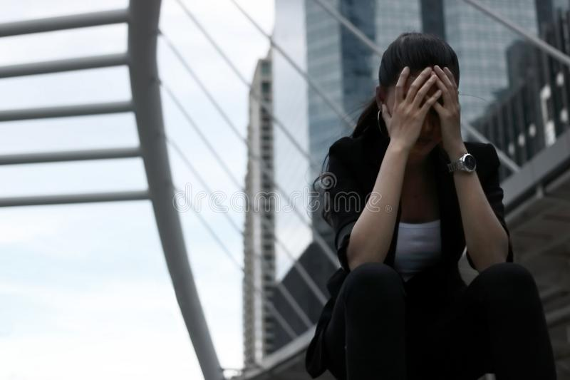 Low key toned image of depressed stressed young Asian business woman covering face with hands suffering from trouble stock photos