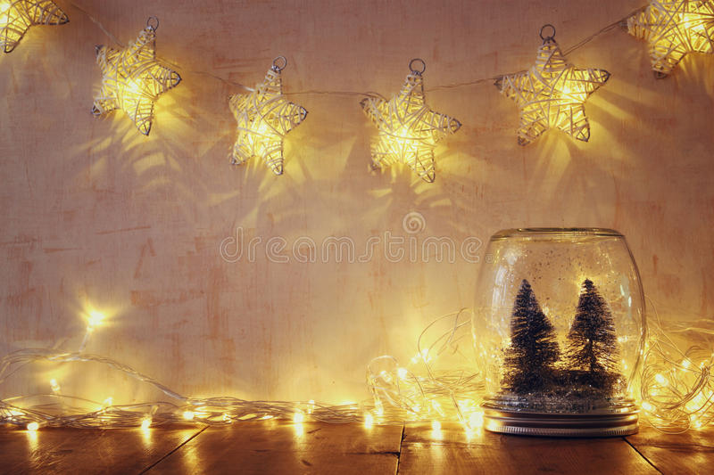 Low key and vintage filtered image of christmas trees in mason jar with garland warm lights royalty free stock photos