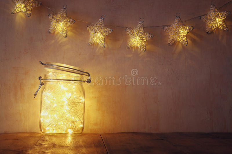 Low key and vintage filtered image of fairy lights in mason jar with. selective focus.  stock photos