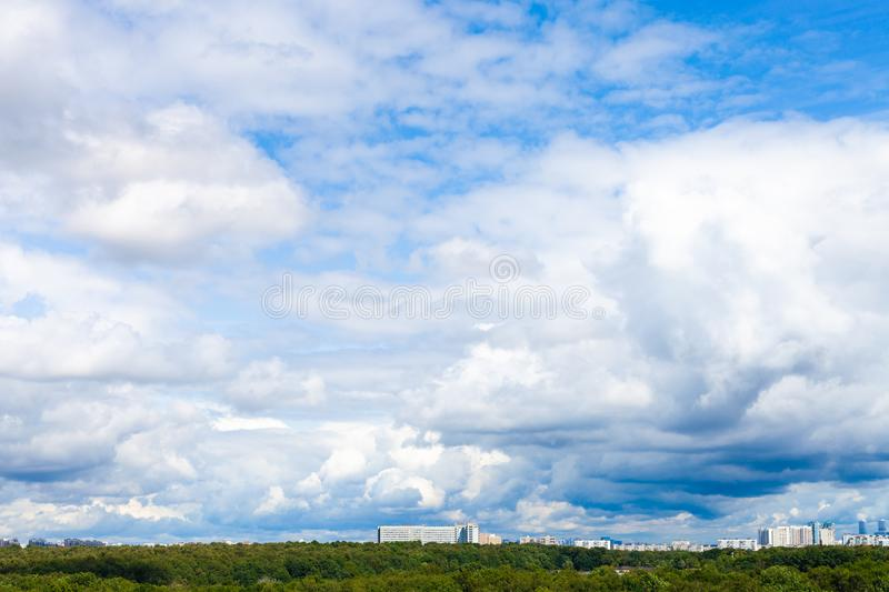 low large white clouds in blue sky over city park royalty free stock photo