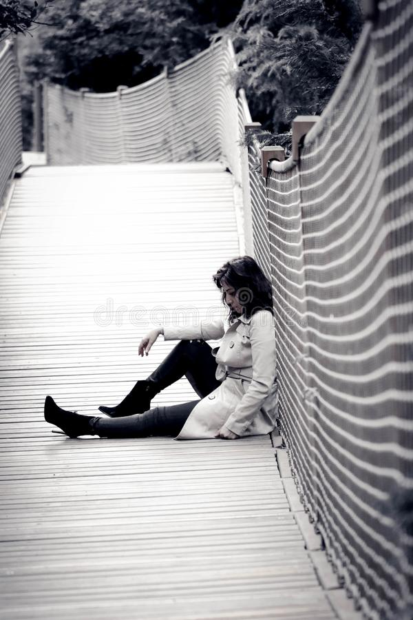 Low Light Photo of Woman Wearing Trench Coat Sitting Against Wall stock image