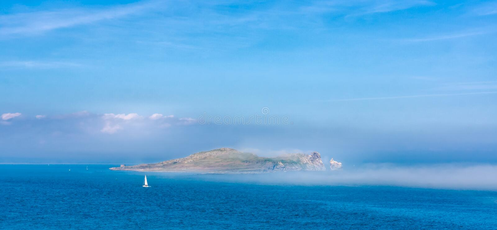 Low lying mist covering Irelands Eye island, view from Howth, Ireland stock photos
