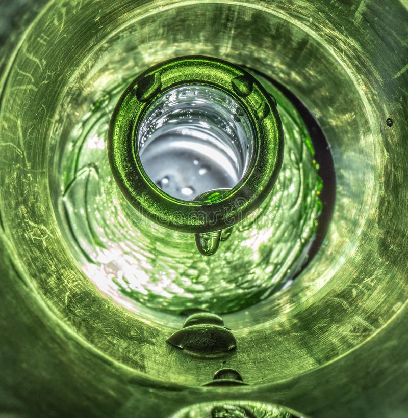 Low Perspective Macro Shot on Dripping Wet Bottle. Unique macro photography of a vibrant green surreal bottle dripping wet with water in a rugged green lit royalty free stock image