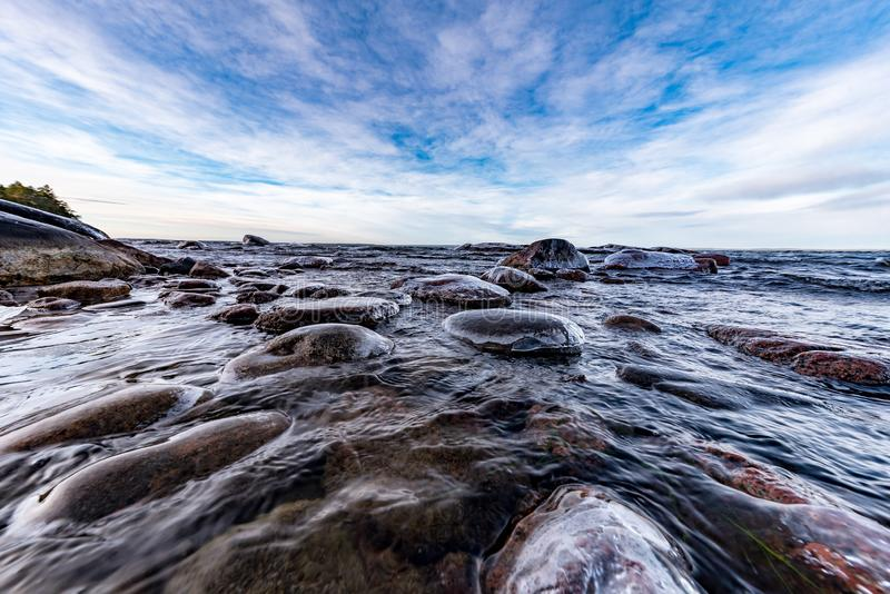 Low perspective over icy rocks in lake. With blue and cloudy sky royalty free stock images