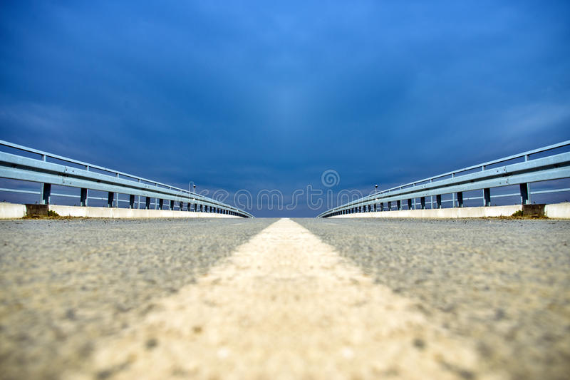 Low perspective of overpass road. Low angle perspective of overpass road over blue sky stock photo