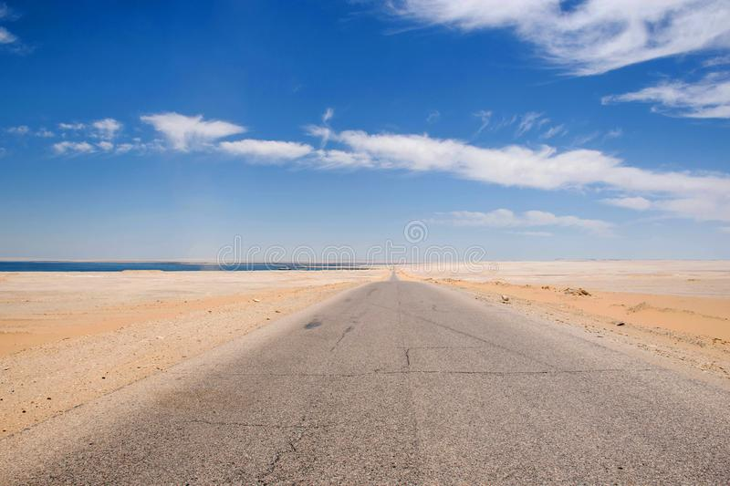 Low perspective road in the desert of fayoum egypt. Straight road towards the horizon with lake on the left. Road trip background, long straight desert road stock photo