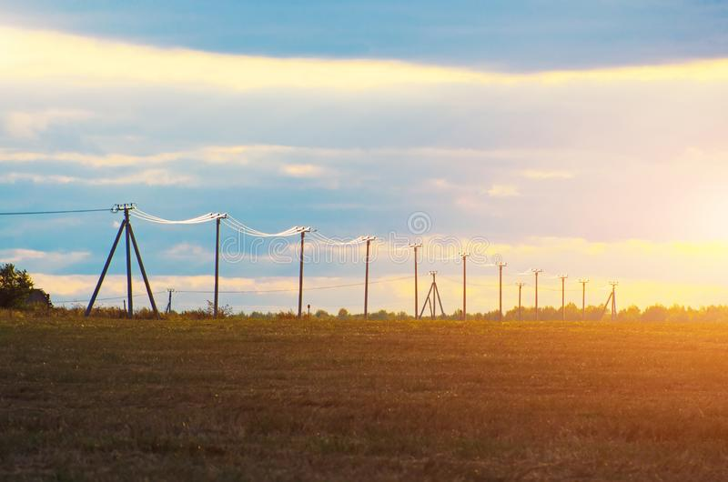 Low poles with electric wires shining on a sunny sunset in a field of horizon.  stock photos