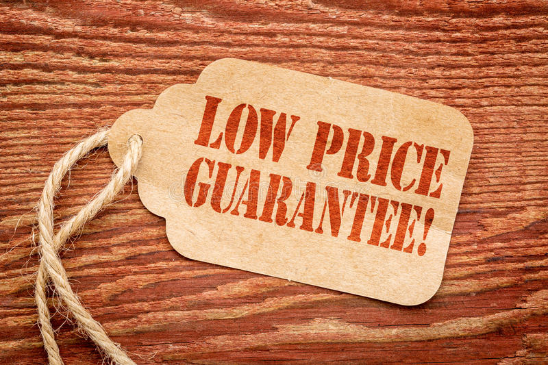 Low price guarantee on paper price tag. Low price guarantee - sign on paper price tag against a rustic red barn wood stock images