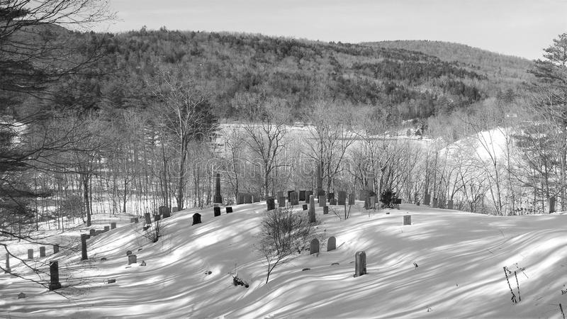 Black and white winter cemetery in early morning sun. A low rise with mountain in the background houses numerous headstones and footstones in an old graveyard royalty free stock photo