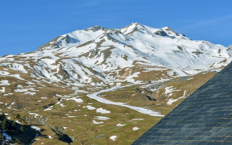 Low season half snowy mountains at a ski resort royalty free stock image