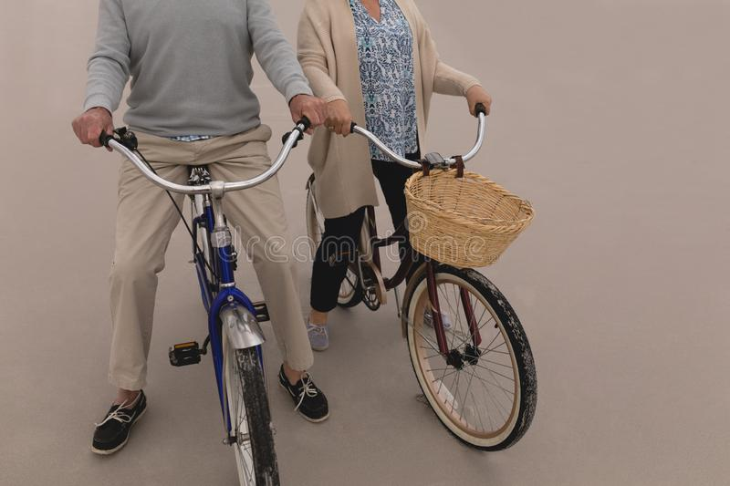 Happy senior couple riding a bicycle on the sand at the beach royalty free stock photography
