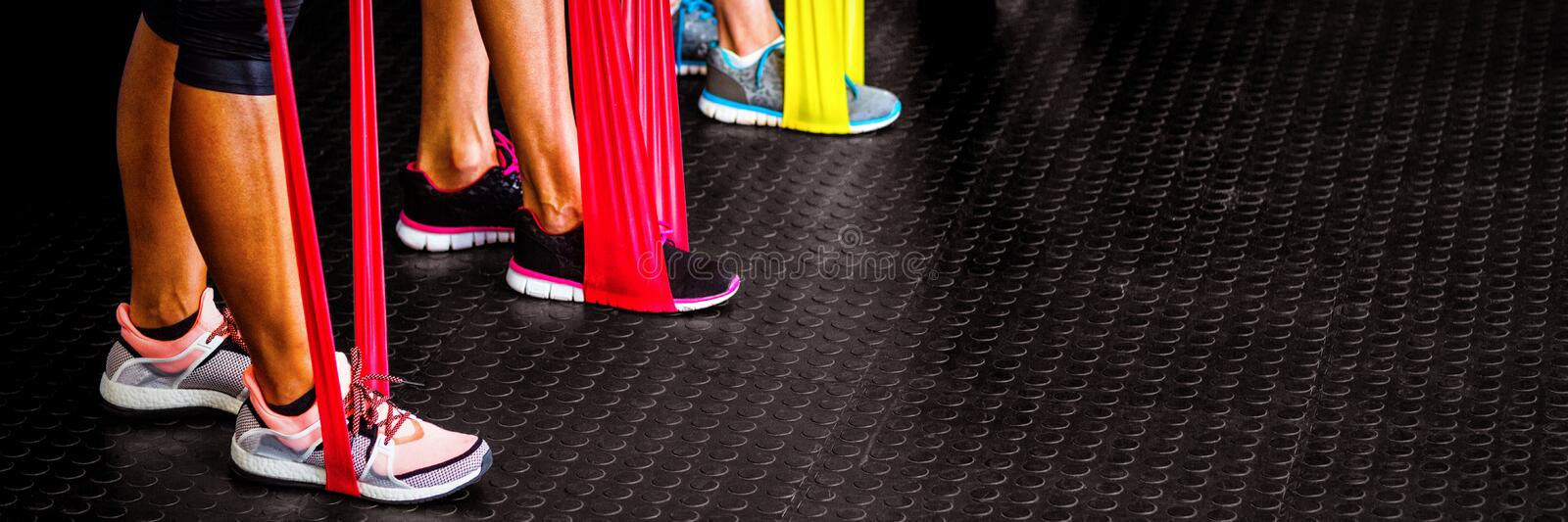 Low section of athletes exercising with resistance band royalty free stock image