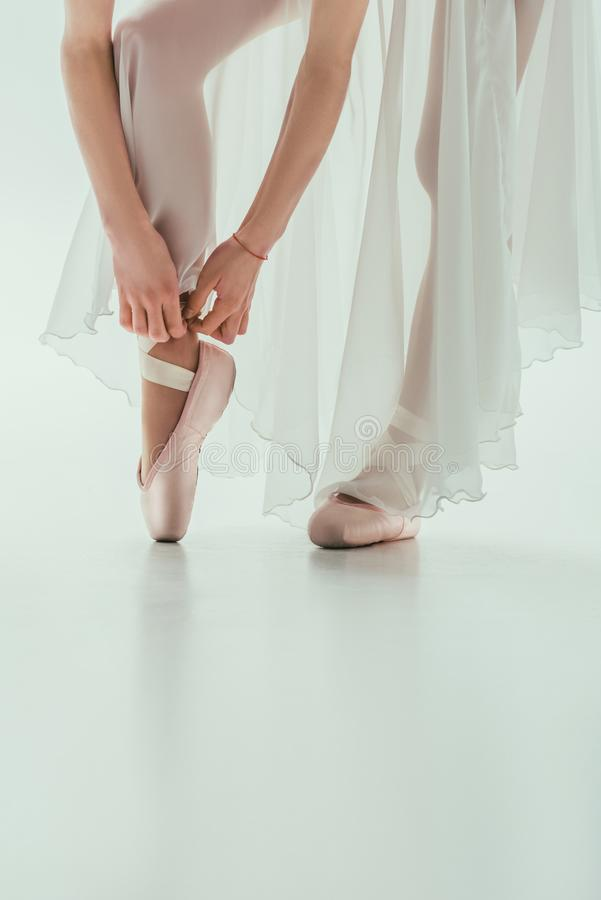Low section of ballerina wearing ballet shoes,. Isolated on white royalty free stock images