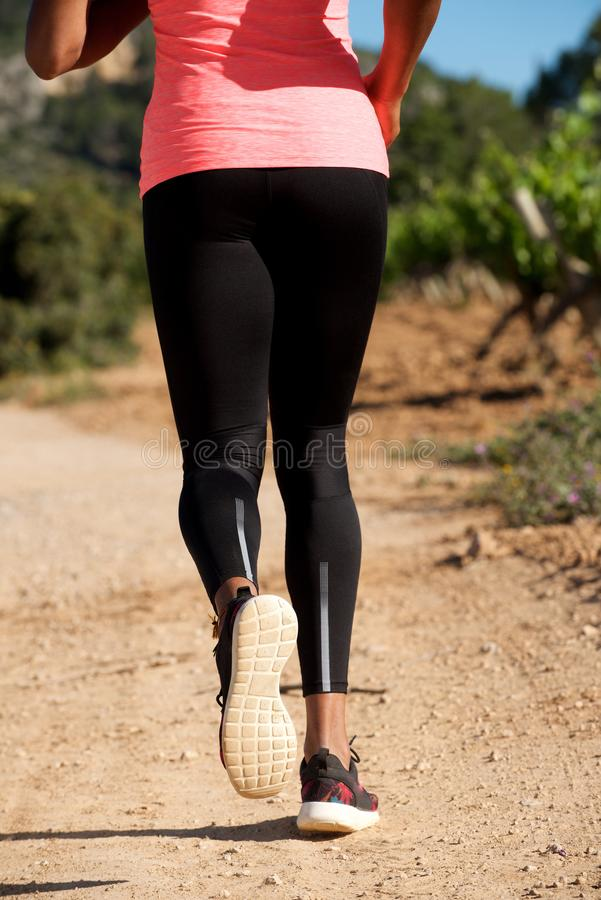 Low section from behind of woman running on dirt road outdoors. Low section portrait from behind of woman running on dirt road outdoors stock photo
