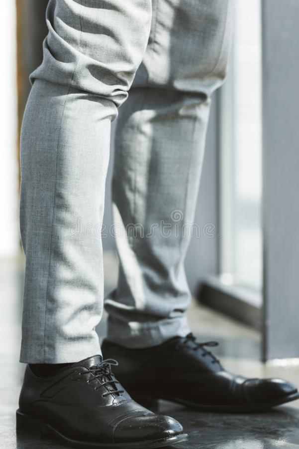 low section of businessman standing in fashionable leather shoes and pants royalty free stock photo