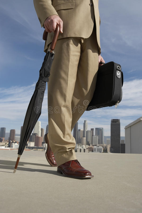 Low section Of Businessman With Umbrella And Briefcase Against Buildings stock photos