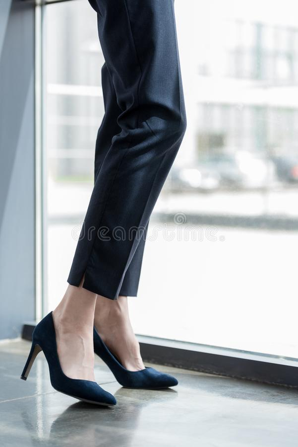 Low section of businesswoman in high heeled shoes standing. Near window royalty free stock images