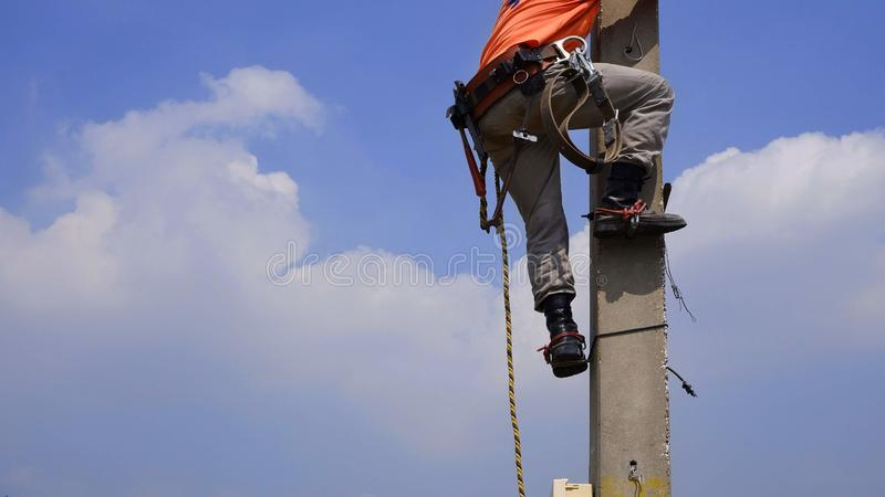 Low section of electrician with tools and equipment is climbing on electric power pole royalty free stock image