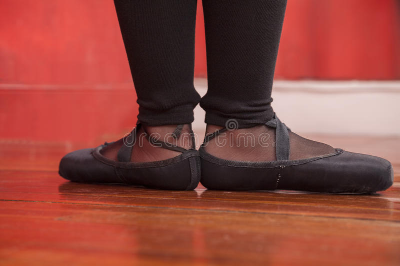 Low Section Of Female Dancer Wearing Ballet Shoes. While standing on hardwood floor in studio stock images