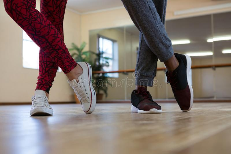 Low section of friends practicing dance on floor. Low section of friends practicing dance on wooden floor in studio stock photography