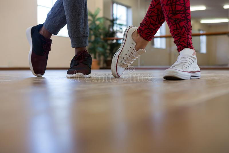 Low section of friends rehearsing dance on floor. Low section of friends rehearsing dance on wooden floor in studio royalty free stock image