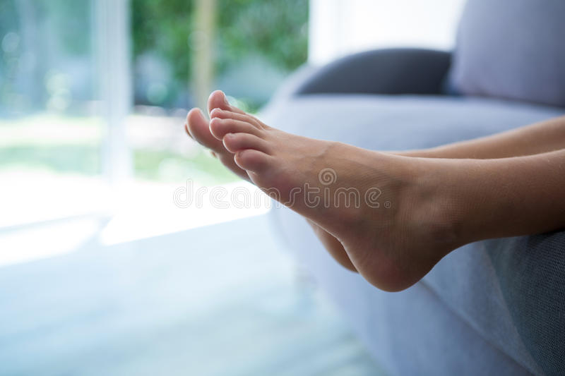 Low section of girl relaxing on sofa. At home royalty free stock photo