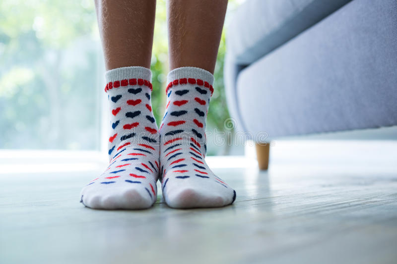 Low section of girl wearing socks. While standing by sofa at home royalty free stock photography