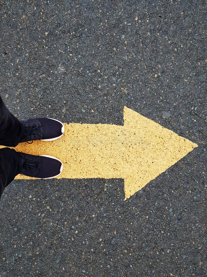 Low section of a man standing on a yellow arrow on asphalt. Low section of a man wearing a black shoes standing on a yellow arrow on asphalt stock photo