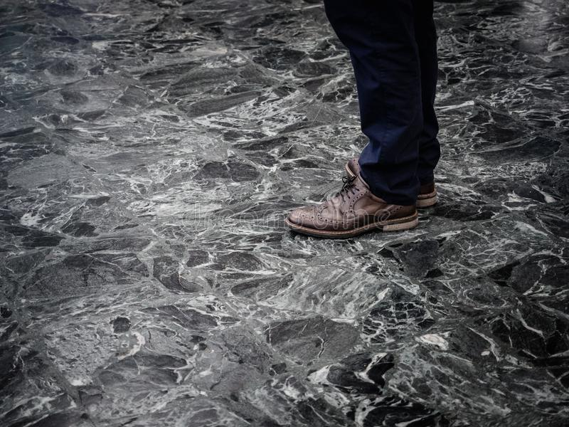 Low section of man wearing smart leather shoes standing on marble floor indoors.  stock image