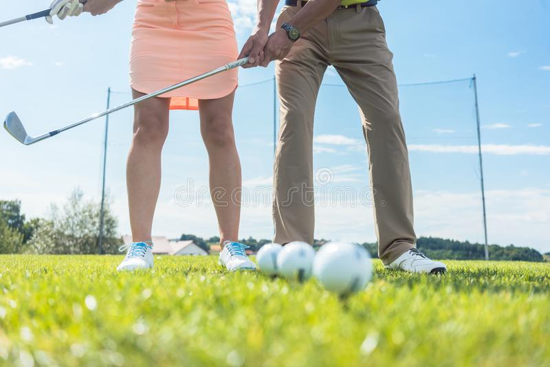 Low section of man and woman holding iron clubs while practicing stock photo