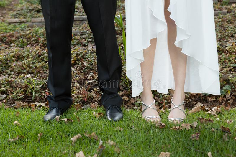 Low section of newlywed couple standing on field royalty free stock photos
