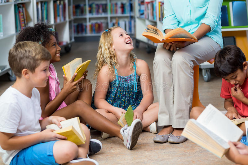 Low section of teacher with children reading books. Low section of female teacher with smiling children reading books in library stock images